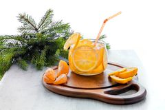 与冰、柠檬水与切片桔子和普通话的橙色冷的饮料在一个木立场的一块透明玻璃在a 库存图片