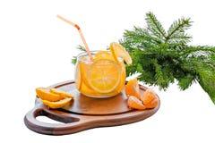 与冰、柠檬水与切片桔子和普通话的橙色冷的饮料在一个木立场的一块透明玻璃在a 库存照片