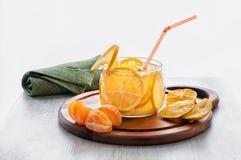 与冰、柠檬水与切片桔子和普通话的橙色冷的饮料在水平一个木的立场的一个透明碗 免版税库存照片