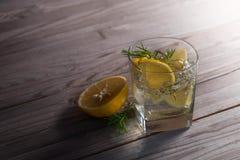 与冰、补品和柠檬的杜松子酒在一张老木桌上 免版税图库摄影