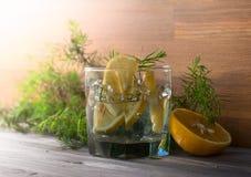 与冰、补品和柠檬的杜松子酒在一张老木桌上 图库摄影