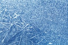 与冰冷的织地不很细样式的抽象结冰的窗口,蓝色玻璃表面崩裂了冰宏指令视图 库存照片