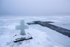 与冰十字架的美好的冬天风景在冻河在有雾的早晨IV 库存照片