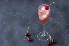 与冰和一棵樱桃的冷却的樱桃鸡尾酒在香槟玻璃 免版税库存图片