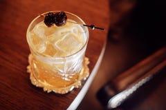 与冰和樱桃的富有的黄色鸡尾酒在棍子 免版税库存图片