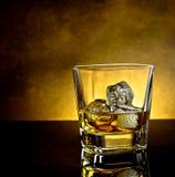 与冰和温暖的光和黑桌,温暖的大气的威士忌酒玻璃 库存图片