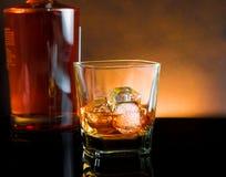 与冰和温暖的光的威士忌酒玻璃在黑桌,温暖的大气上 库存照片