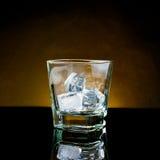 与冰和温暖的光的空的威士忌酒玻璃在黑桌上 免版税库存图片