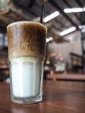 与冰和牛奶的咖啡在木桌上的玻璃杯子 免版税库存图片