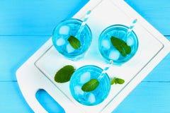 与冰和薄菏的蓝色鸡尾酒在一个白色木板的玻璃在一张蓝色桌上 顶视图 免版税库存照片