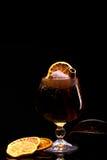 与冰块、柠檬和肉桂条的鸡尾酒在黑背景的一块玻璃 免版税库存图片