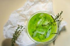 与冰块和绿色分支的一份绿色饮料在m的一块玻璃 库存照片