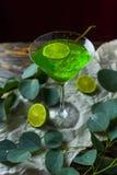 与冰块的一份绿色饮料在mojito的一块玻璃在被弄皱的w 免版税库存图片