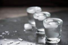 与冰块的伏特加酒射击在黑石头, 免版税图库摄影
