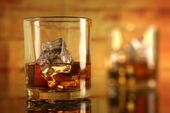 与冰块的变冷的威士忌酒玻璃与bokeh 免版税库存照片