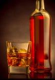 与冰块的威士忌酒在黑背景,温暖的大气的玻璃近的瓶 免版税图库摄影