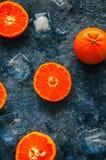 与冰块的新鲜的成熟tangerins普通话在一块蓝宝石 免版税库存图片