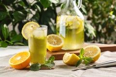 与冰块的柑橘薄荷的柠檬水在葡萄酒玻璃水瓶旁边的玻璃杯 夏天饮料Limoncello 图库摄影