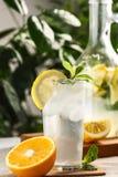 与冰块的柑橘薄荷的柠檬水在葡萄酒玻璃水瓶旁边的玻璃杯 夏天饮料Limoncello 免版税图库摄影