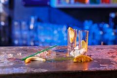 与冰块的溢出的鸡尾酒在蓝色颜色 免版税库存照片