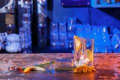 与冰块的溢出的鸡尾酒在蓝色颜色 免版税库存图片