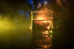 与冰块的选择聚焦纯净的威士忌酒在黑暗的有雾的背景酒精饮料概念的威士忌酒玻璃里面 免版税库存图片