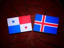 与冰岛旗子的巴拿马旗子在被隔绝的树桩 免版税库存照片