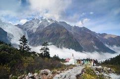 与冰川和薄雾的Stupa在海螺沟全国冰川森林公园 免版税图库摄影