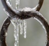 与冰柱的冻结的铜圆环 免版税库存照片