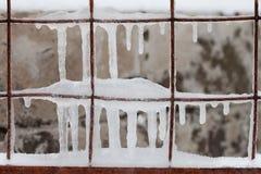 与冰柱的冻金属篱芭滤网导线 冬天季节区域概念 冰冷的天气背景 宏观看法软的焦点 免版税库存图片