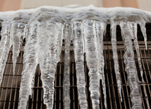 与冰柱水落管的冷气候概念在金属网 宏观看法 软绵绵地集中 免版税库存图片