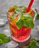 与冰橙色切片和片断的一份轻的碳酸化合的樱桃饮料,薄荷叶和止在热的干渴的鸡尾酒管 库存照片