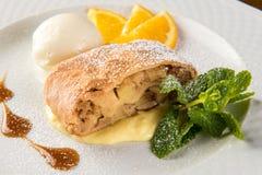 与冰淇凌和桔子的苹果果馅奶酪卷在白色板材 库存照片