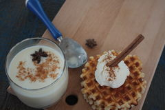 与冰淇凌和牛奶,桂香,在蓝色木背景的茴香的奶蛋烘饼 免版税图库摄影