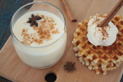 与冰淇凌和牛奶,桂香,在蓝色木背景的茴香的奶蛋烘饼 免版税库存图片