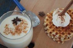 与冰淇凌和牛奶,桂香,在蓝色木背景的茴香的奶蛋烘饼 免版税库存照片