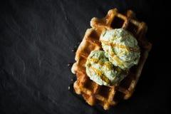 与冰淇凌的比利时华夫饼干在黑暗的石背景顶视图 免版税库存图片