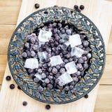 与冰片断的冷冻黑醋栗在葡萄酒板材的 库存照片