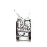 与冰的冷水倾吐水对在白色的玻璃 免版税库存图片