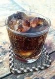 与冰的可乐在木背景的一块玻璃 库存图片