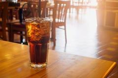 与冰的可乐玻璃在木桌上在餐馆背景中 免版税库存照片