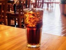 与冰的可乐玻璃在木桌上在餐馆 免版税库存图片