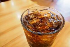 与冰的可乐玻璃在木桌上在餐馆 图库摄影