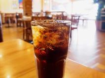 与冰的可乐玻璃在木桌上在餐馆 免版税库存照片