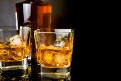 与冰的威士忌酒在瓶前面的玻璃在黑背景 免版税库存照片