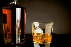 与冰的威士忌酒在黑暗的背景的玻璃近的瓶 免版税库存照片