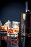 与冰的威士忌酒在玻璃临近在黑背景和光色彩蓝色的瓶 库存图片