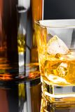 与冰的威士忌酒在黑背景的玻璃近的瓶 库存图片