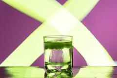 与冰的液体在反射性表面上的一块玻璃在带红色背景 图库摄影