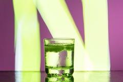 与冰的液体在反射性表面上的一块玻璃在带红色背景 免版税库存图片